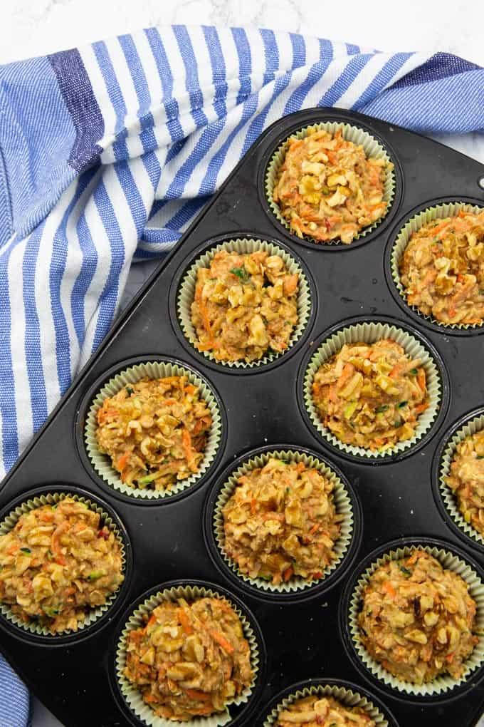 Zucchini Muffins in einer schwarzen Backform mit einem blau weißen Küchentuch im Hintergrund