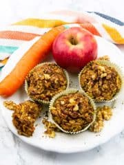 Zucchini Muffins auf einem weißen Teller mit einer Karotte und einem Apfel im Hintergrund