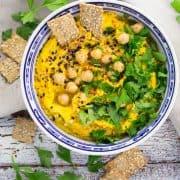 eine Schüssel Kürbis Hummus mit gehackter Petersilie, Sesam und Crackern