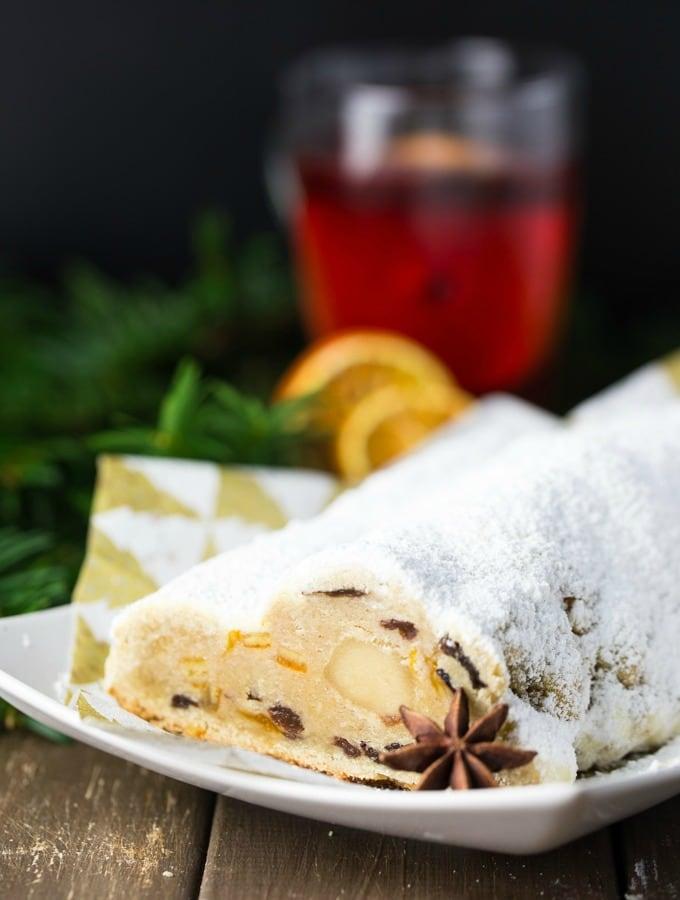Veganer Stollen mit Marzipan auf einem weißen Teller mit einer Tasse Glühwein und getrockneten Orangenscheiben im Hintergrund