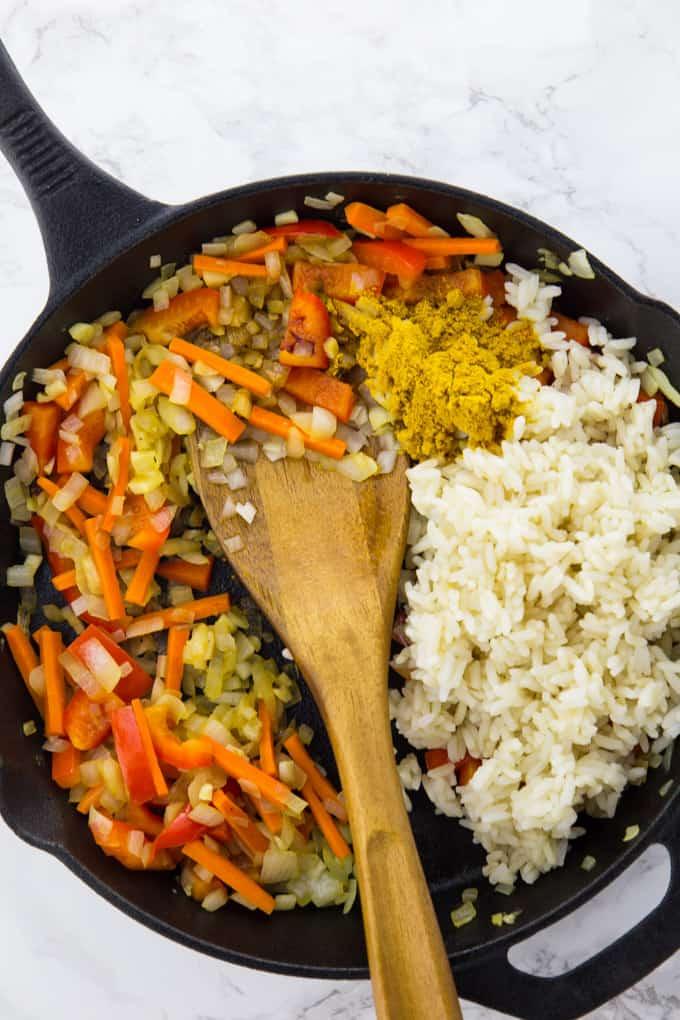 Gekochter Reis, Karotten- und Paprikastreifen, Zwiebeln und Currypulver in einer Gusseisenpfanne