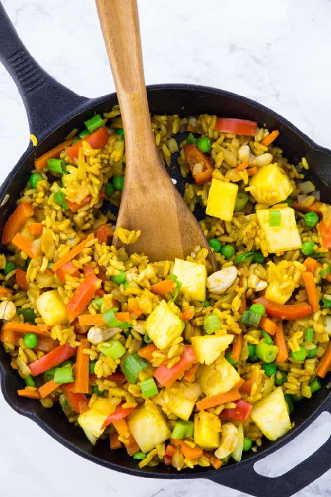 Der gebratene Reis wird mit einem Holzlöffel in der Pfanne umgerührt