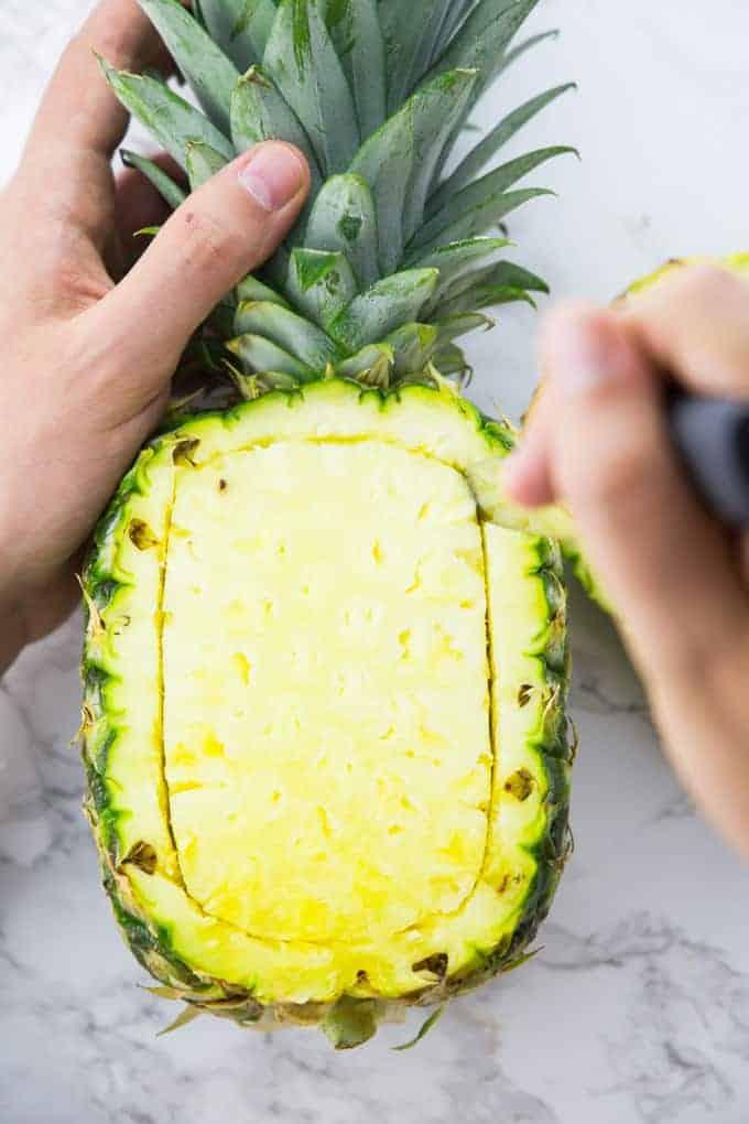 Eine Ananas wird mit einem scharfen ausgeschnitten