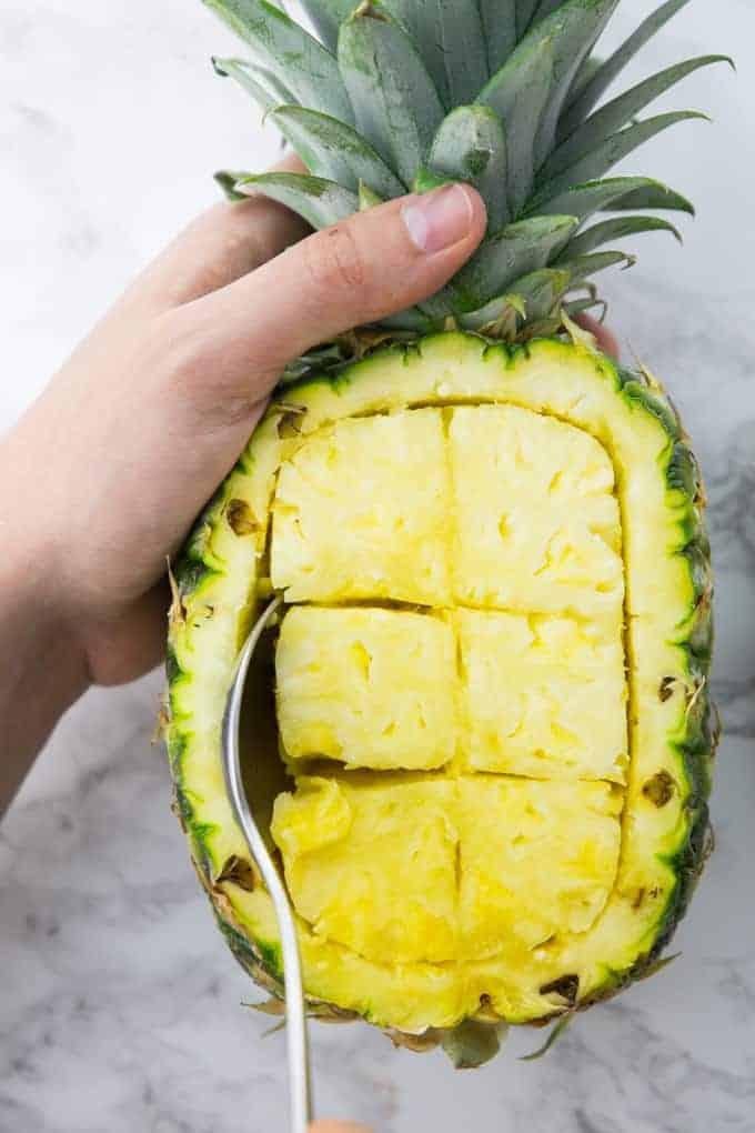 Ananasstücke werden mit einem Löffel aus einer Ananas gelöffelt