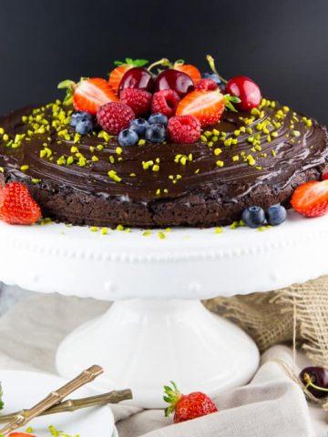 ein veganer Schokokuchen auf einer weißen Kuchenplatte mit frischen Beeren