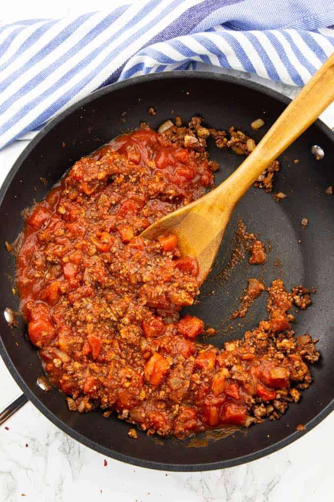 Zubereitung von Chili sin Carne in einer schwarzen Pfanne mit einem Holzlöffel