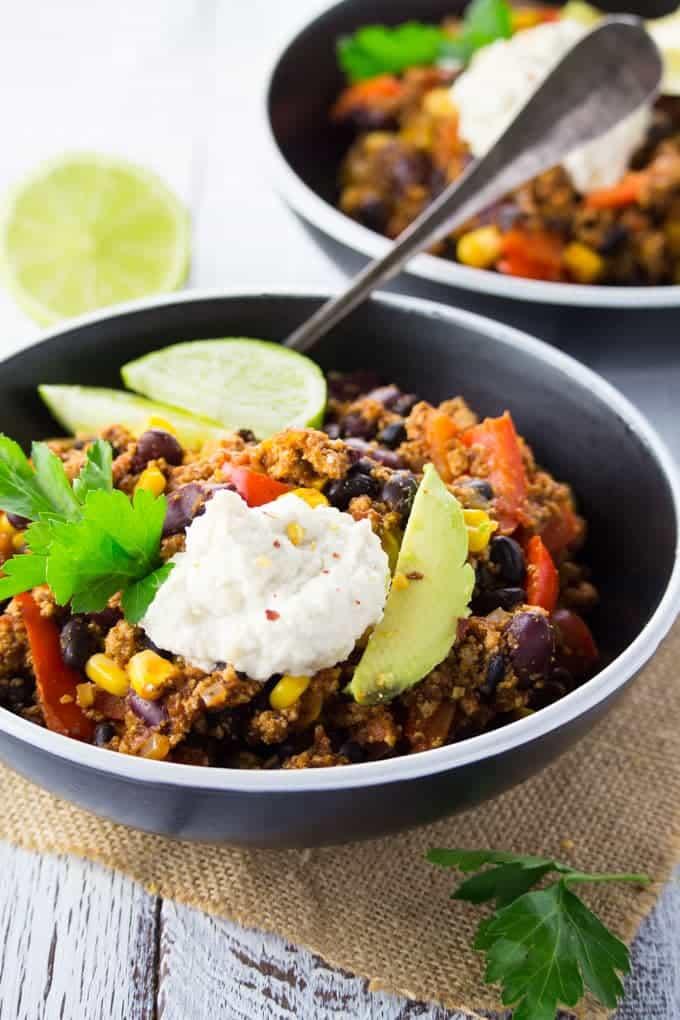 Chili Sin Carne in zwei schwarzen Schüssel mit Avocado und Cashew Sour Cream auf einem weißen Holzbrett