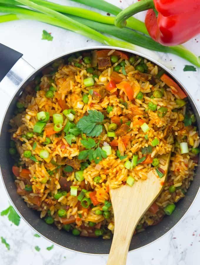 Djuvec Reis in einem schwarzen Topf auf einer Marmorarbeitsplatte mit einem Holzlöffel sowie Frühlingszwiebeln und einer roten Paprika neben dem Topf