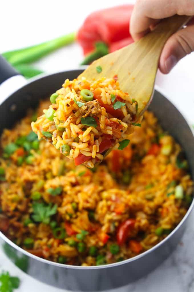 Djuvec Reis in einem schwarzen Topf mit einer Hand, die einen Holzlöffel mit Djuvec Reis hält