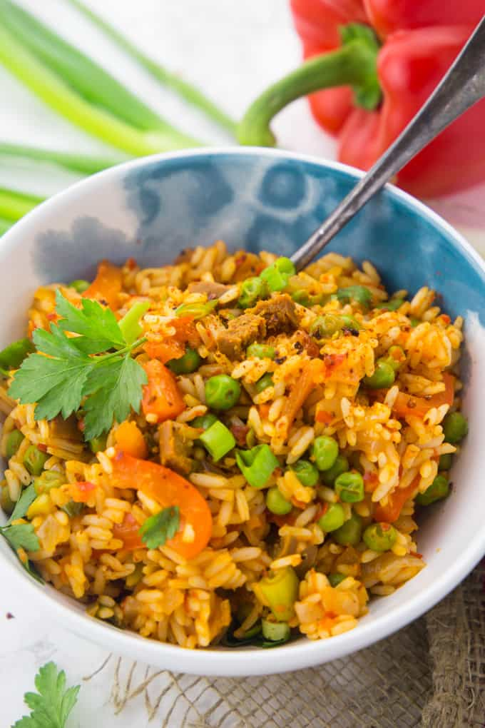 Djuvec Reis in einer weiß blauen Schüssel mit einer Gabel mit einer Paprika und Frühlingszwiebeln im Hintergrund