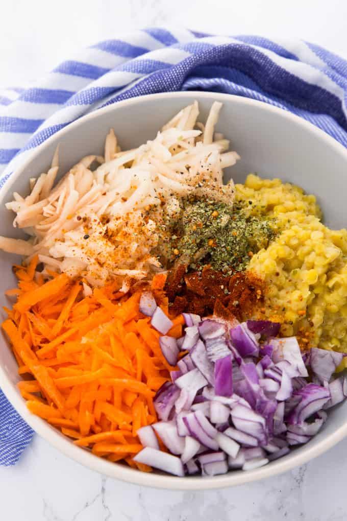 Geriebene Kartoffel, Karotten, rote Linsen und Zwiebeln in einer Schüssel