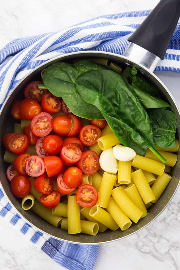 Rigatoni, Tomaten, Spinat und Knoblauch in einem Kochtopf