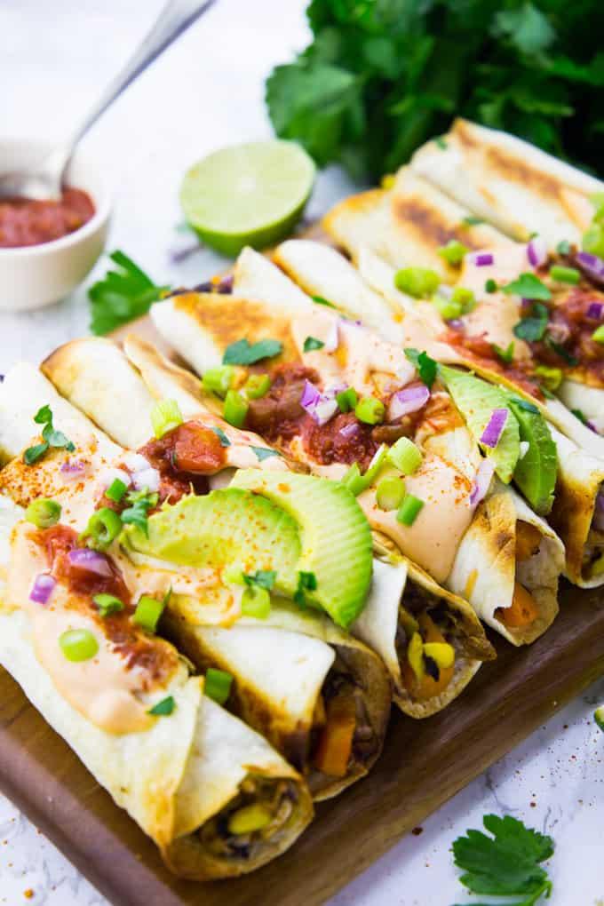 Taquitos mit Avocado und frischem Koriander auf einem Holzbrett