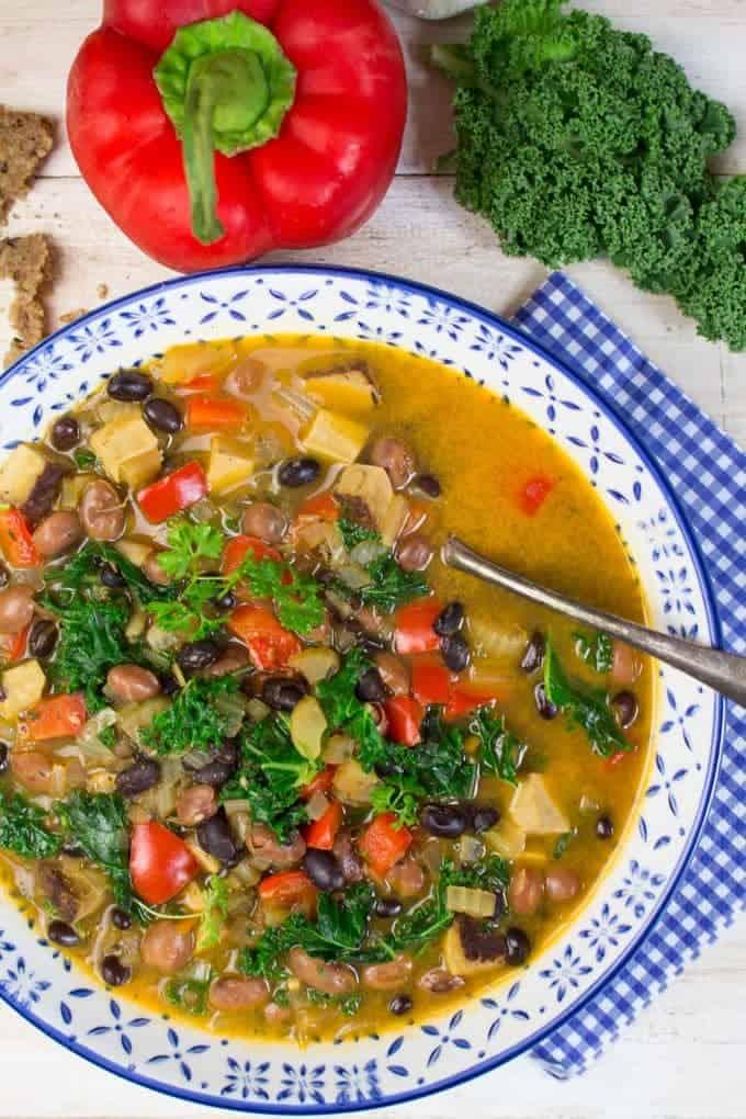 Eine Suppenschüssel gefüllt mit einem Grünkohl Bohnen Eintopf und Brot als Beilage