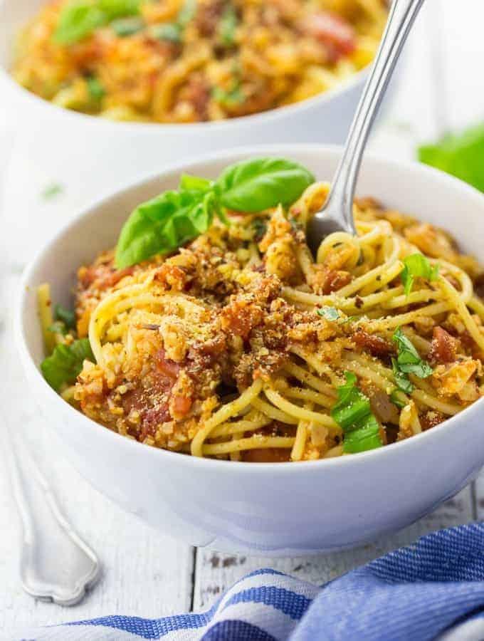 Eine weiße Schüssel mit Spaghetti und Blumenkohlbolognese mit einer Gabel