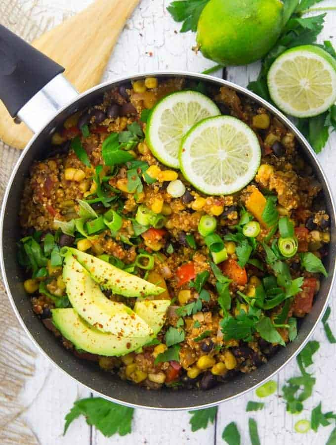 Ein Topf gefüllt mit Quinoa-Chili und Avocadostückchen sowie Limetten neben dem Topf