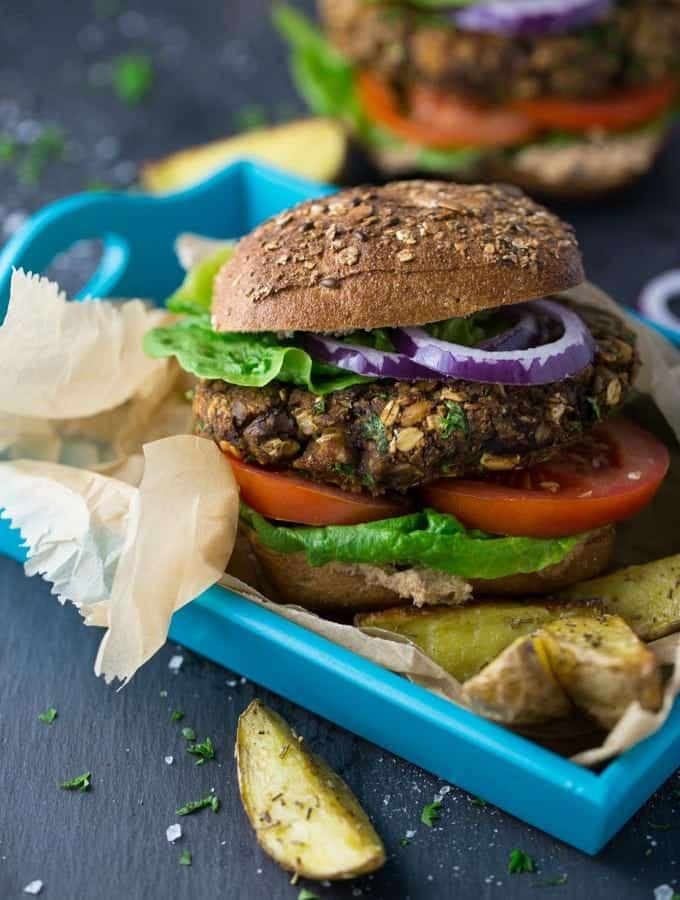 Ein veganer Pilzburger mit Kartoffelecken in einem blauen Servierkorb