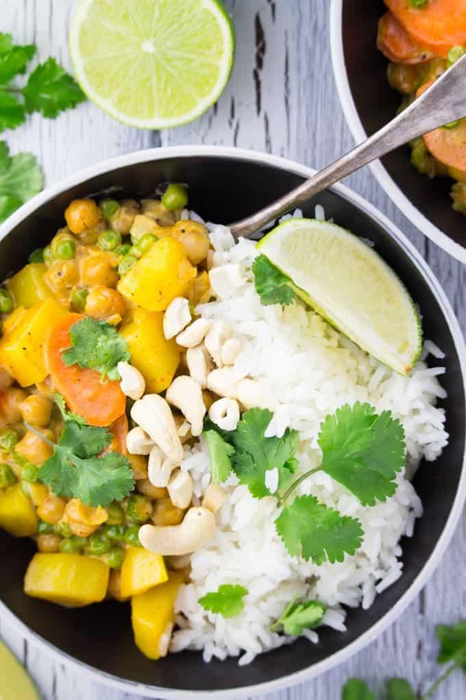 Eine Schüssel mit weißem Reis und veganem Curry mit Kichererbsen und Kartoffeln