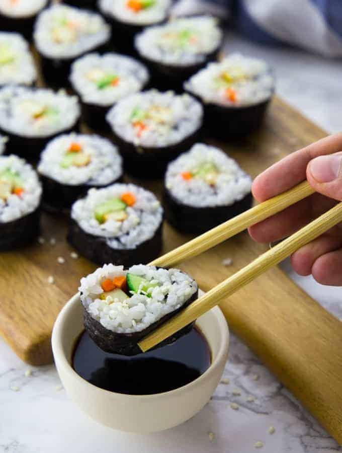 Ein Sushi wird mit Stäbchen in Sojasauce gedippt