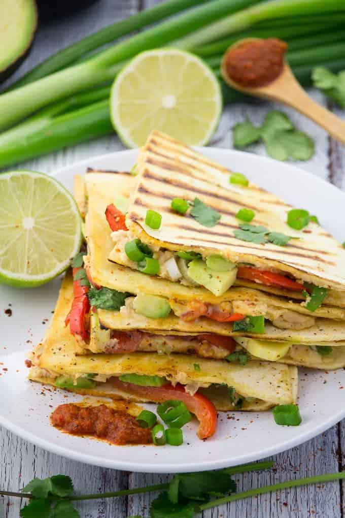 Vier vegane Quesadillas auf einem weißen Teller mit Harissasauce