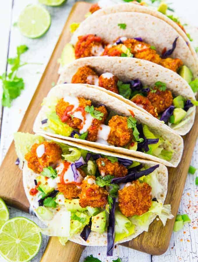 Eine hölzerne Servierplatte mit Tacos gefüllt mit Blumenkohl Wings