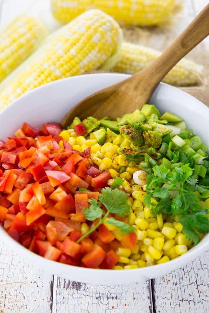 Gewürfelte Paprika, Avocado, Frühlingszwiebel und Mais in einer Schüssel