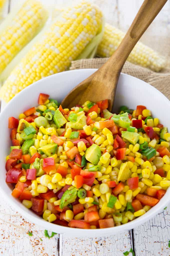 Gewürfelte Paprika, Avocado, Frühlingszwiebel und Mais werden in einer Schüssel vermischt