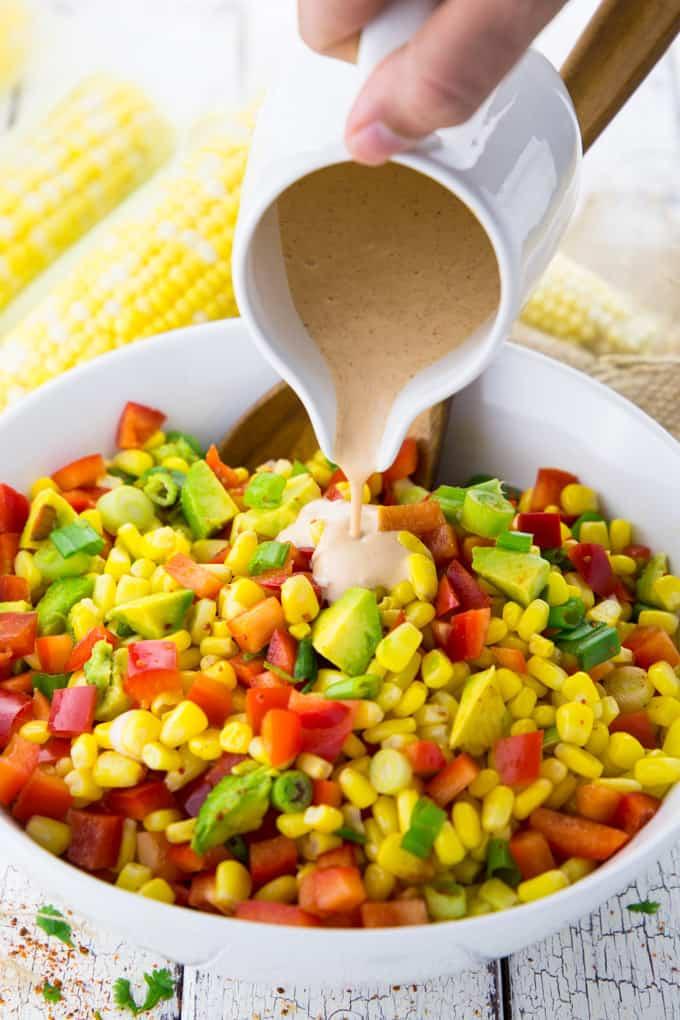 Chipotle Dressing wird über Maissalat gegossen