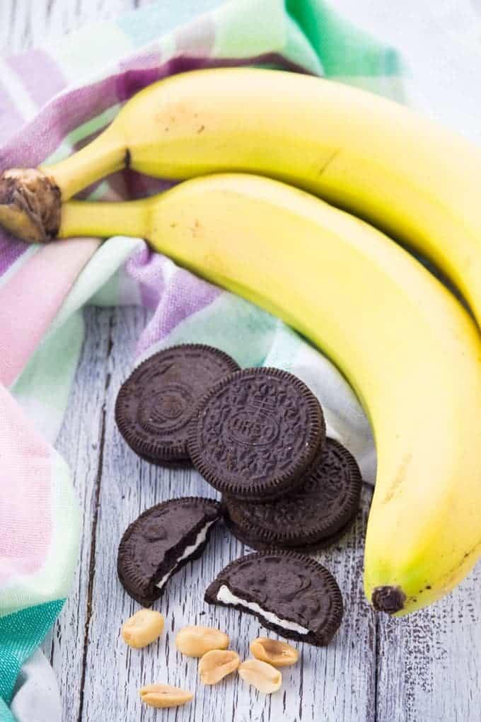 Bananen, Oreo Kekse und Erdnüsse auf einem Holzbrett