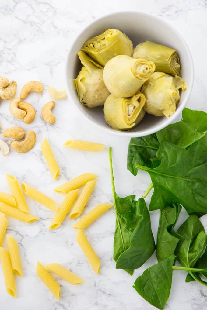 Nudeln, Spinat, Artischocken und Cashews auf einer Marmorplatte