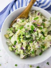 Veganer Kartoffelsalat in einer Schüssel mit Holzlöffel