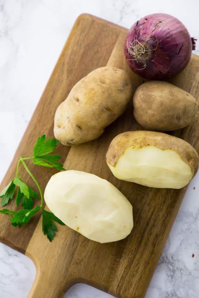 Geschälte Kartoffeln auf einem Holzbrett