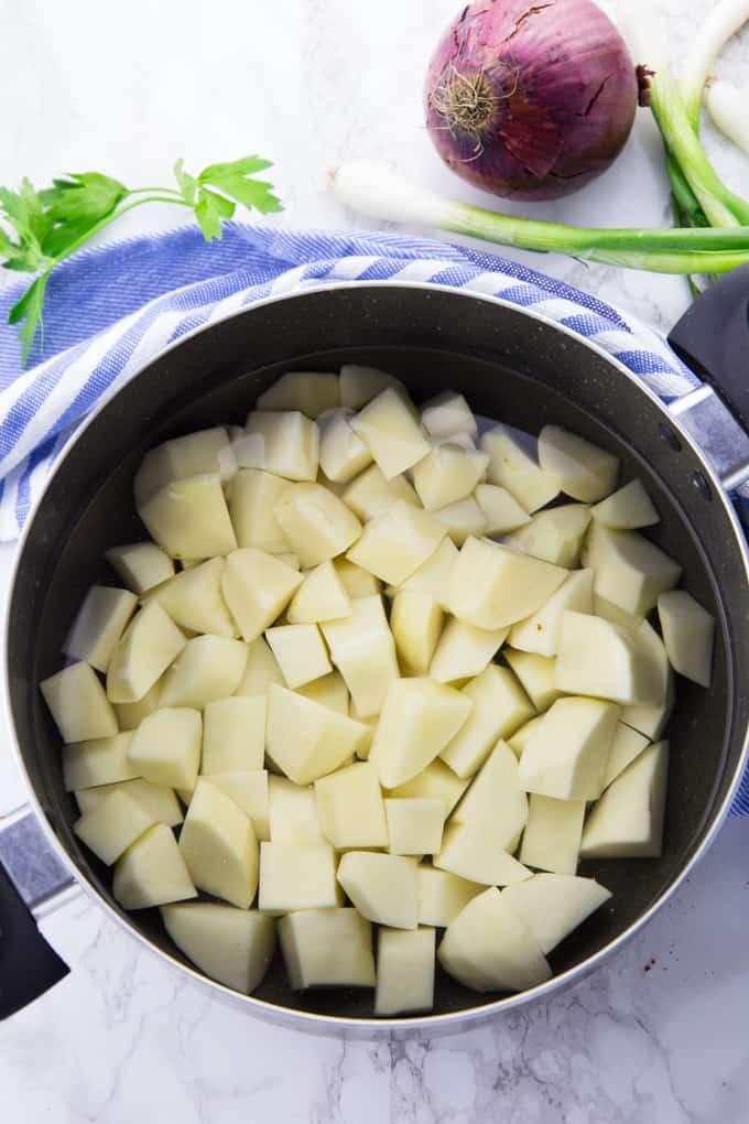 Kartoffelwürfel in einem Topf mit Wasser