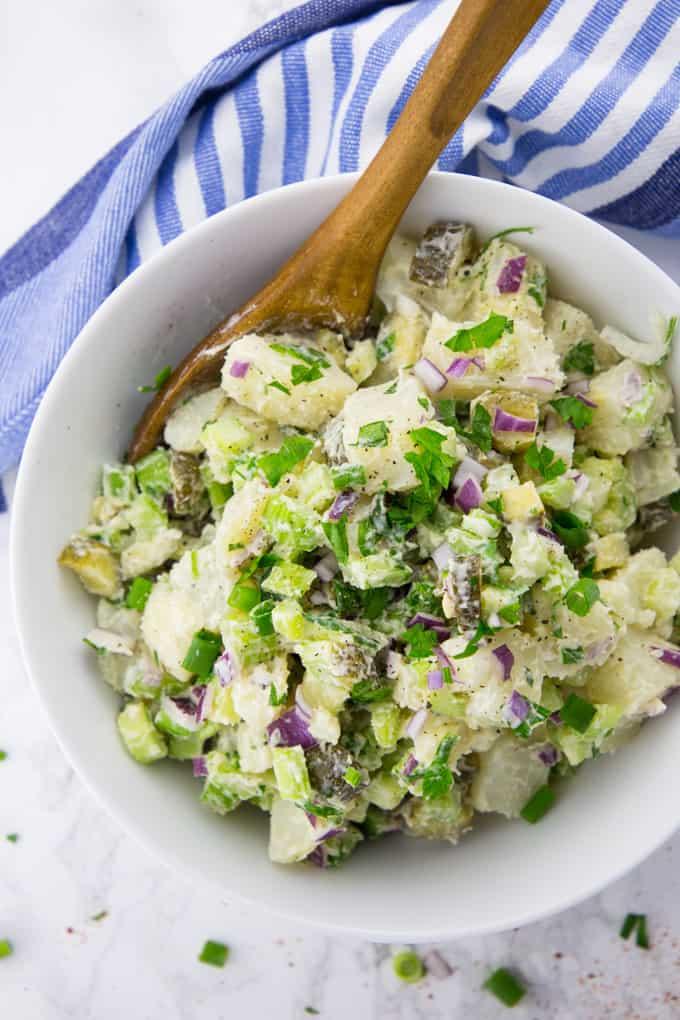 Veganer Kartoffelsalat in einer Schüssel mit einem Holzlöffel