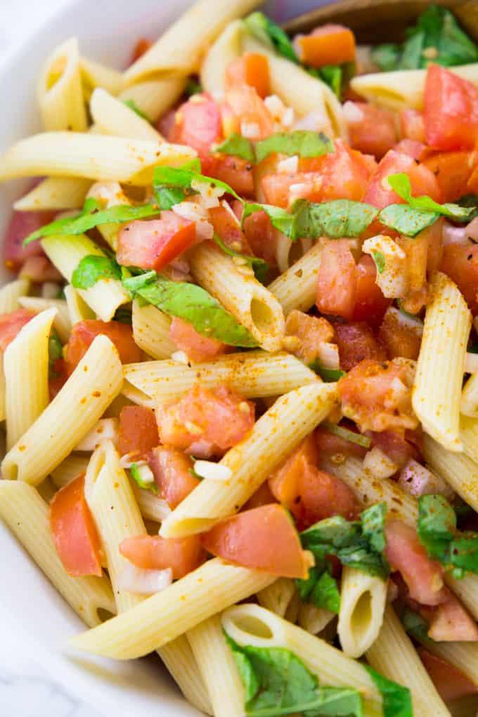 Nahaufnahme eines Nudelsalats mit Tomate und Basilikum