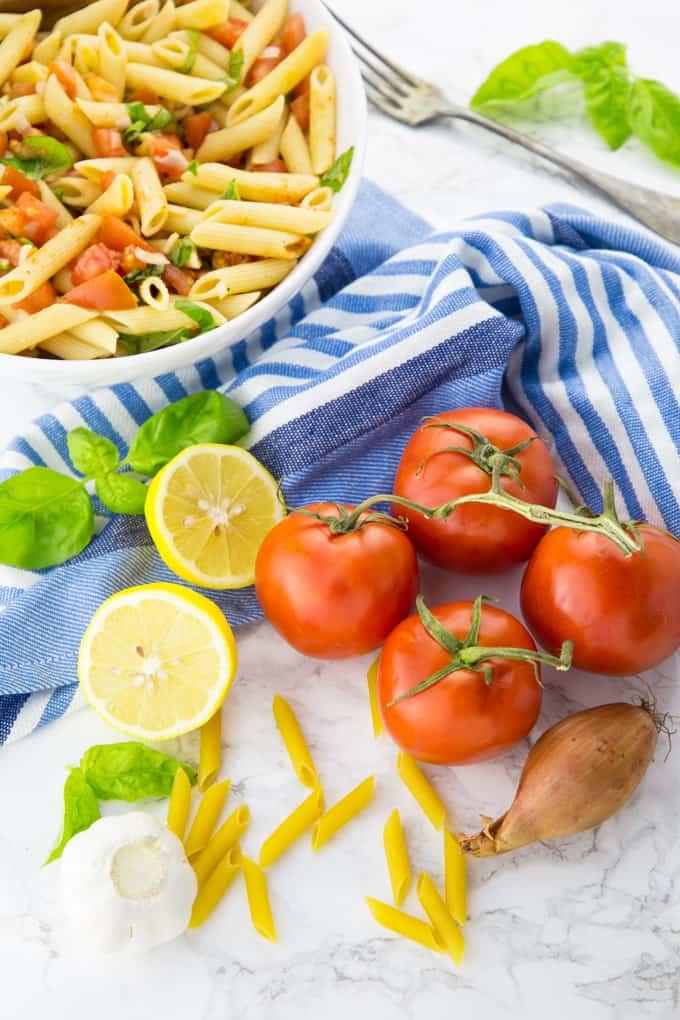 Ungekochte Penne, Tomaten, Zitrone und Knoblauch auf einer Marmorplatte mit Nudelsalat im Hintergrund
