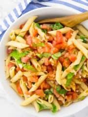 Nudelsalat mit Tomate und Basilikum in einer weißen Schüssel mit Holzlöffel