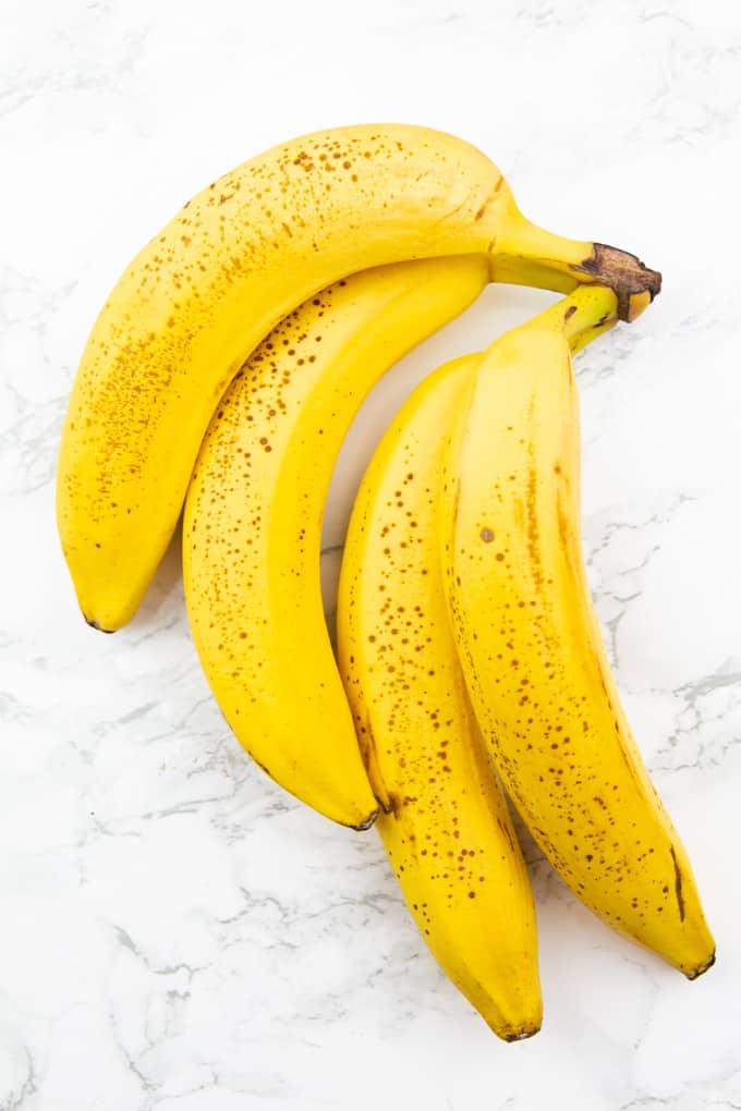 vier reife Bananen auf einer Marmorplatte
