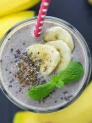 Ein Glas Bananen Smoothie auf einer schwarzen Arbeitsplatte mit Bananen an der Seite
