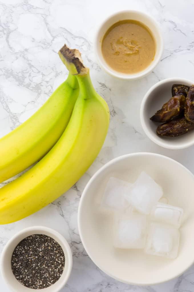 Zutaten für einen Bananen Smoothie auf einer Marmorplatte (Bananen, Erdnussbutter, Chia Samen, Datteln und Eiswürfel)
