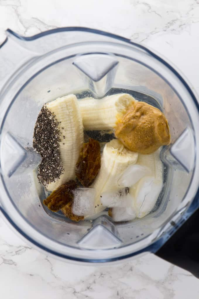 Bananen, Chia Samen, Erdnussbutter und Eiswürfel in einem Mixer