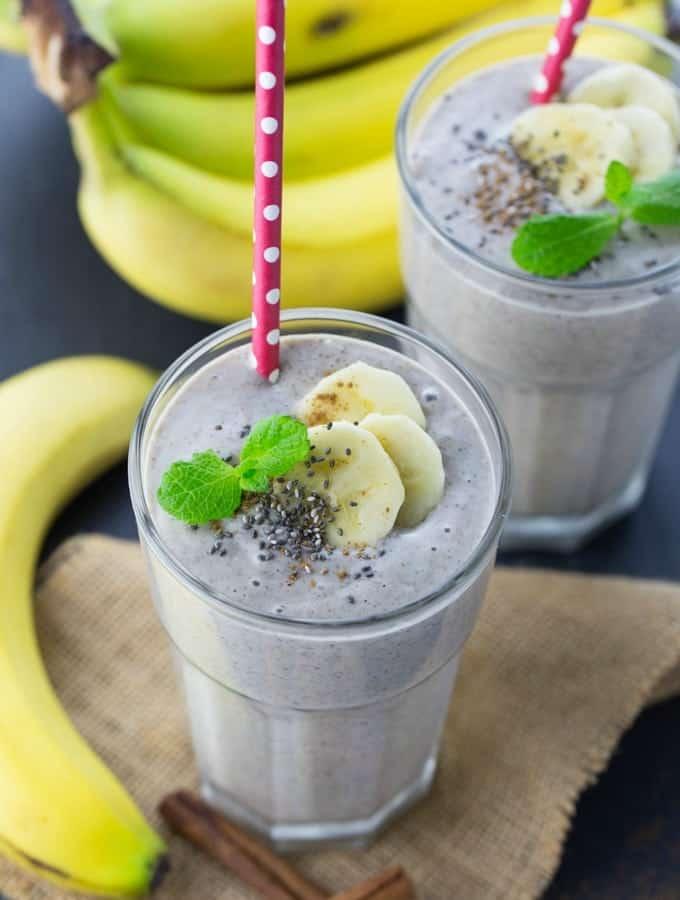 Zwei Gläser Bananen Smoothie mit Strohhalmen und Bananen an der Seite