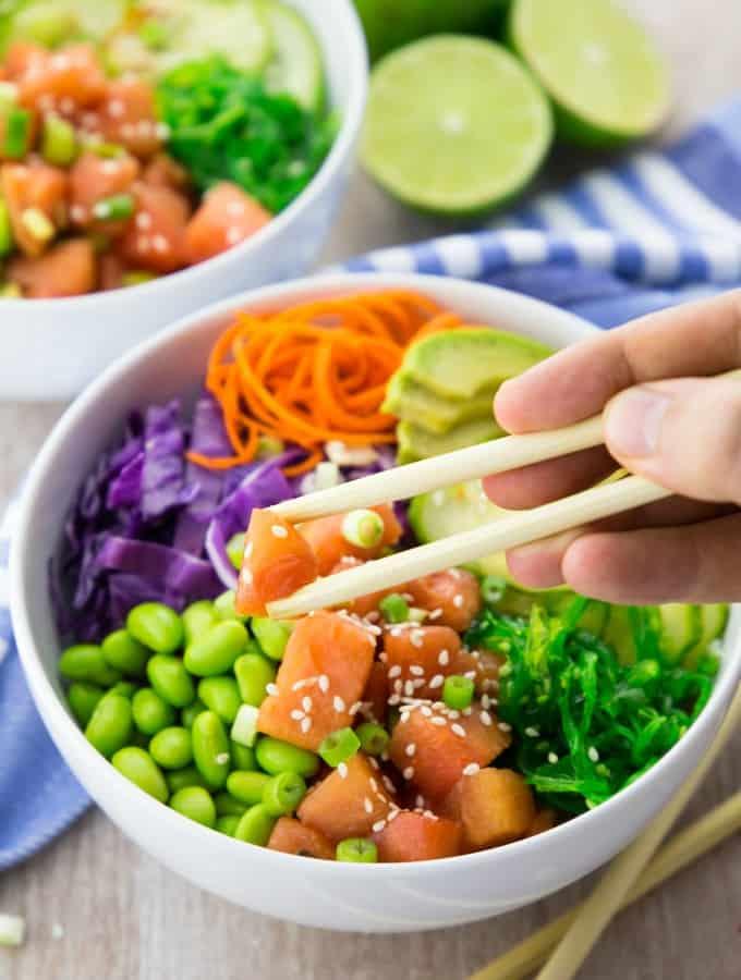 Hand mit Stäbchen nimmt Wassermelonenstück aus Veganer Poke Bowl