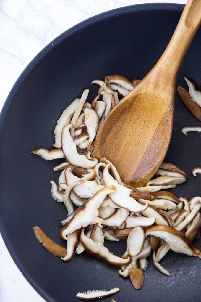 Shiitake-Pilze werden in einer Pfanne angebraten