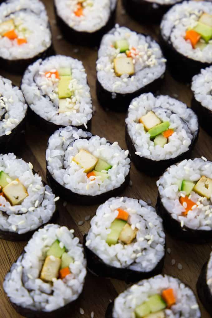 Sushi mit Avocado, Gurke und Tofu auf einem Holzbrett