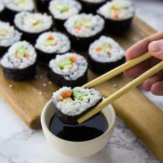 Ein Sushi wird mit Essstäbchen in Sojasauce gedopt mit mehr Sushi im Hintergrund