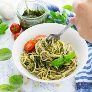 Basilikum Pesto mit Spaghetti in einem weißen Teller mit einer Gabel mit frischen Basilikumblättern und einem Glas mit Pesto im Hintergrund und einer Hand mit Gabel, die die Nudeln aufrollt
