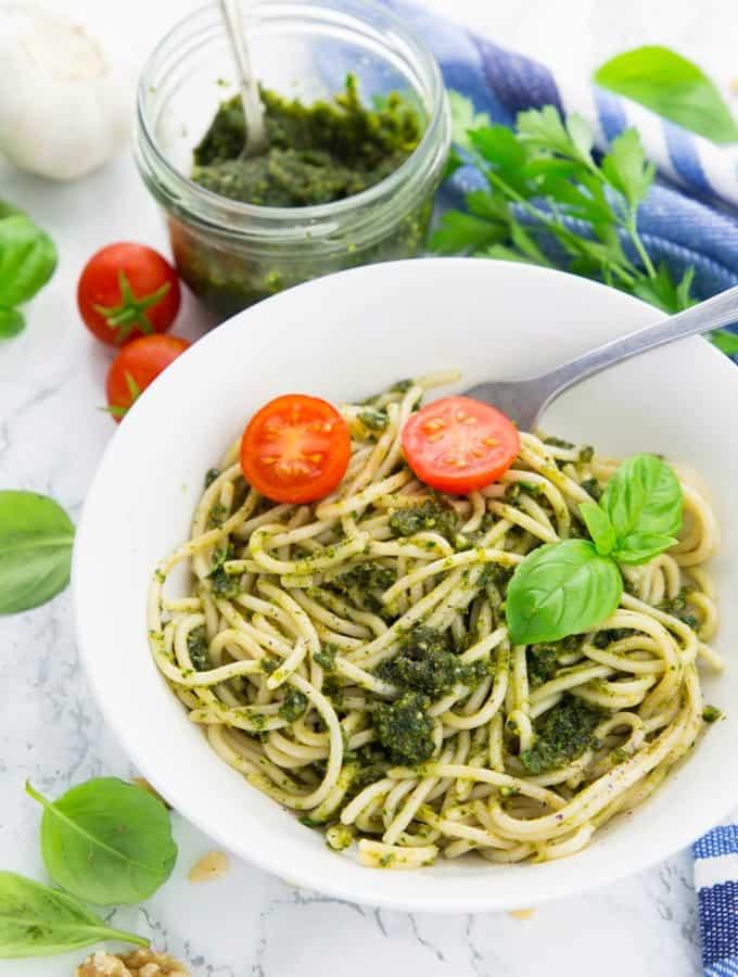 Basilikum Pesto mit Spaghetti in einem weißen Teller mit einer Gabel mit frischen Basilikumblättern und einem Glas mit Pesto im Hintergrund