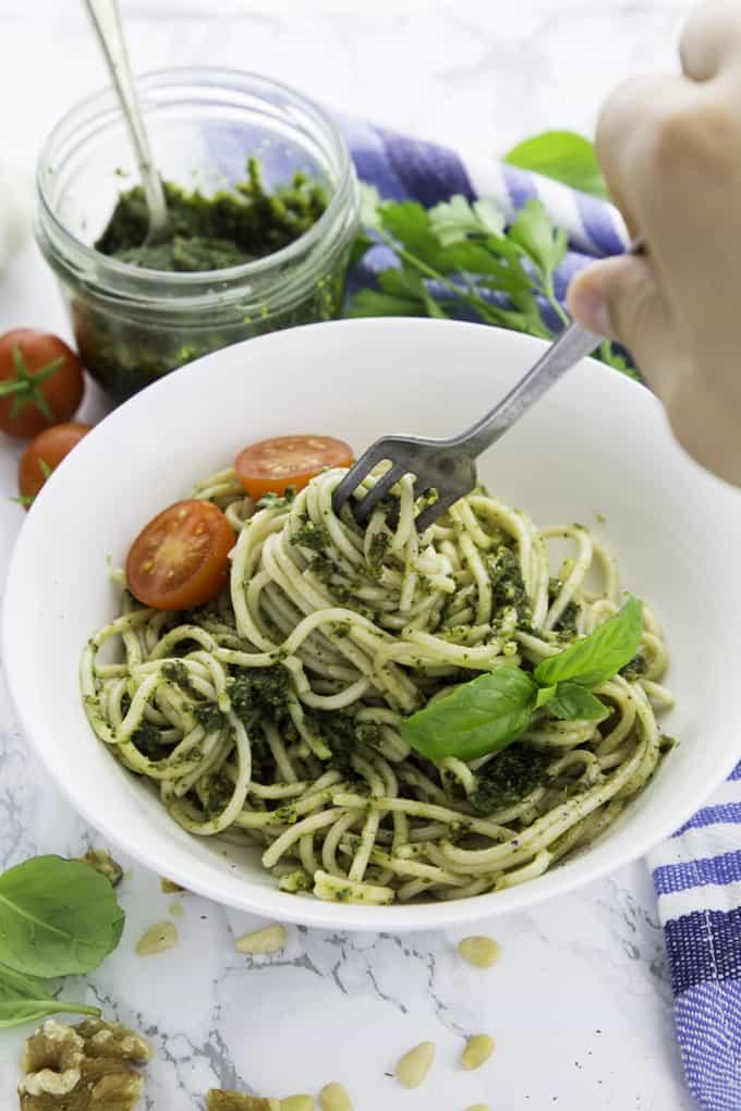 Basilikum Pesto mit Spaghetti in einem weißen Teller mit einer Gabel mit frischen Basilikumblättern und einem Glas mit Pesto im Hintergrund und einer Hand die mit einer Gabel Spaghetti aufrollt
