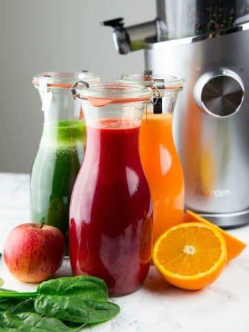 selbstgemachter Saft aus dem Entsafter in drei Flaschen (grün, orange und rot) mit einem Entsafter im Hintergrund